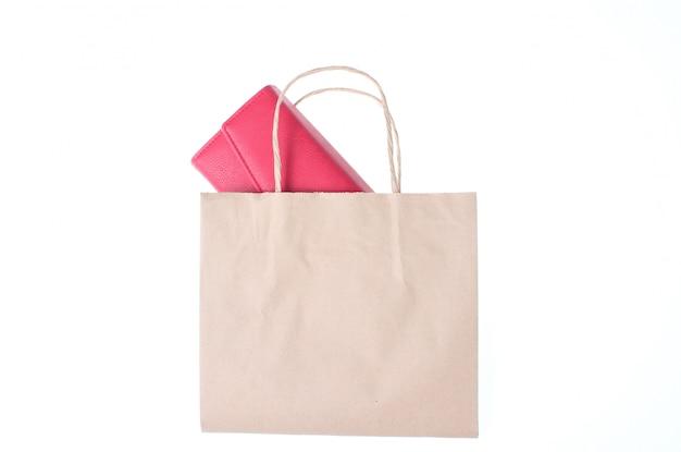 Portefeuille en cuir rouge sur un sac en papier isolé