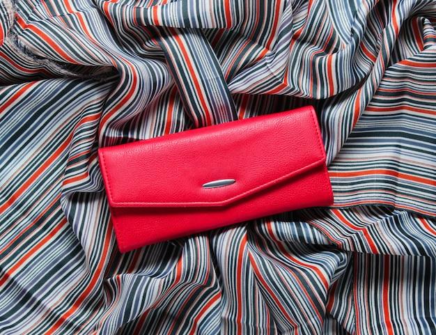 Portefeuille en cuir rouge sur table en tissu.