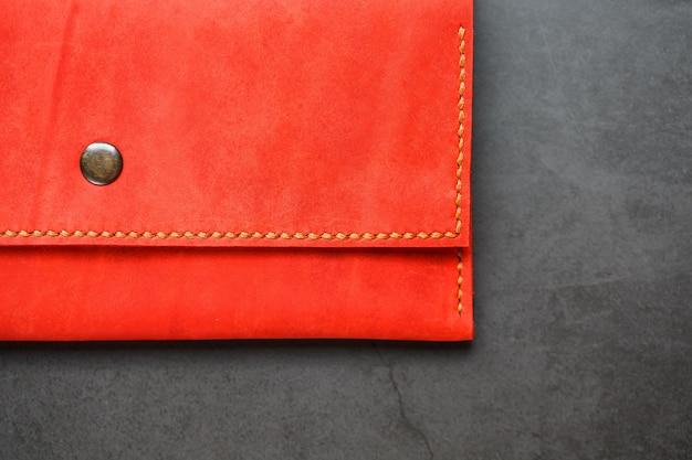 Portefeuille en cuir rouge sur une vue de dessus de fond sombre. gros plan, détails de sac à main, rivet et firmware