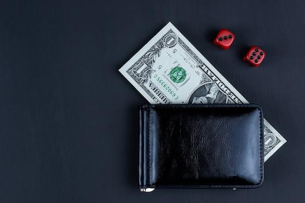 Dés et portefeuille avec un dollar sur fond noir, succès du jeu de casino