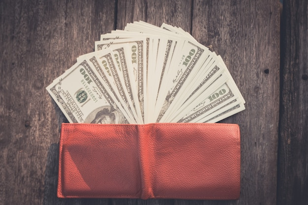 Portefeuille avec des dollars américains sur une table en bois