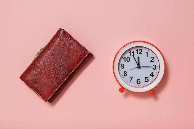 Portefeuille femme en cuir et réveil sur fond rose. le concept de lever le ton le matin.