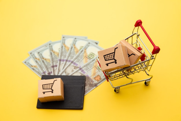 Portefeuille gris avec des billets de cent dollars, des boîtes de livraison et un caddie sur fond jaune
