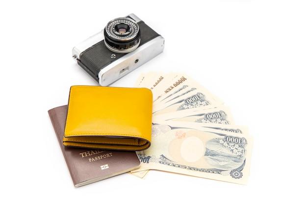 Le portefeuille jaune était placé sur le passeport et les billets de banque et la caméra étaient sur une surface blanche. isolé.