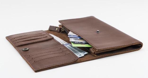Portefeuille marron avec cartes de crédit et billets de cent dollars sur fond blanc
