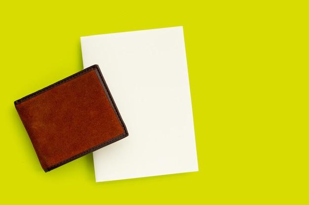 Portefeuille marron avec du papier blanc sur une surface verte