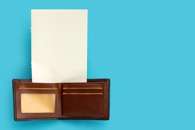 Portefeuille marron avec papier blanc sur surface bleue