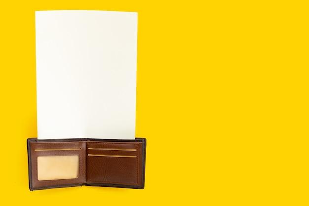 Portefeuille marron avec papier blanc sur surface jaune