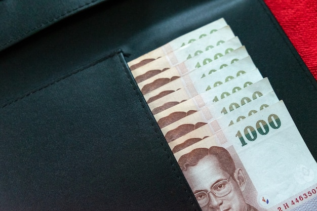 Portefeuille noir et billet de banque thaïlandais sur fond rouge