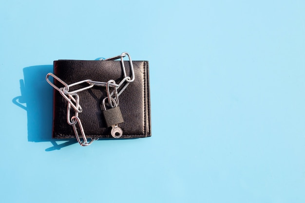 Portefeuille noir en chaînes cadenas fermé sur surface bleue