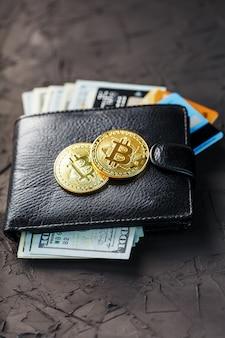 Un portefeuille noir avec des dollars, des cartes électroniques et des bitcoins sur fond noir texturé.