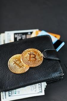Un portefeuille noir avec des dollars, des cartes électroniques et des bitcoins sur un mur texturé noir.
