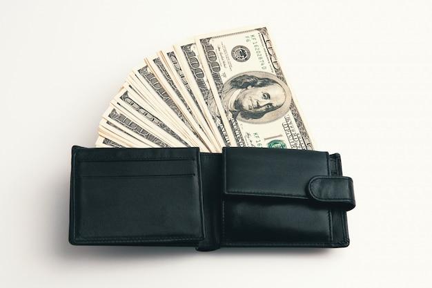 Un portefeuille noir avec des dollars dedans.