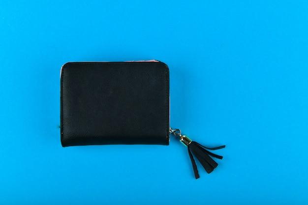 Portefeuille noir sur fond bleu. portefeuille avec un gland noir. un endroit pour écrire. fermer. portefeuille en cuir rose isolé sur un bleu.