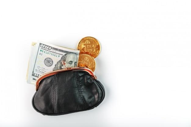 Un portefeuille noir ouvert avec de l'argent, des dollars et des pièces bitcoin sur un mur blanc.