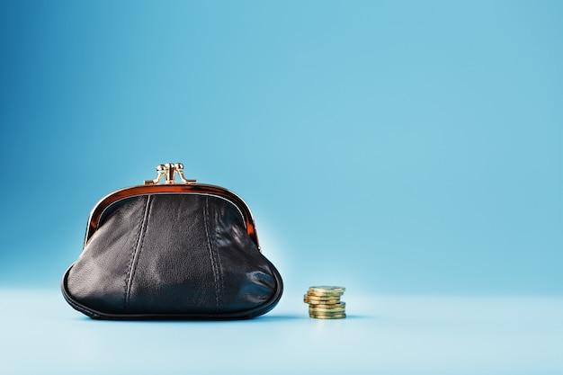 Portefeuille noir avec des pièces sur bleu. budget d'investissement pour l'avenir.