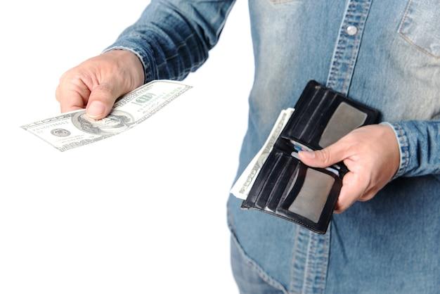 Portefeuille noir qui représente de nombreux dollars américains entre les mains de jeunes qui portent des jeans.