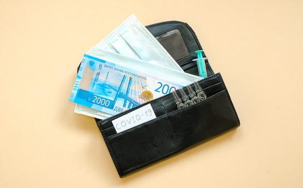 Portefeuille avec roubles russes et masques de protection, ampoules contenant des médicaments