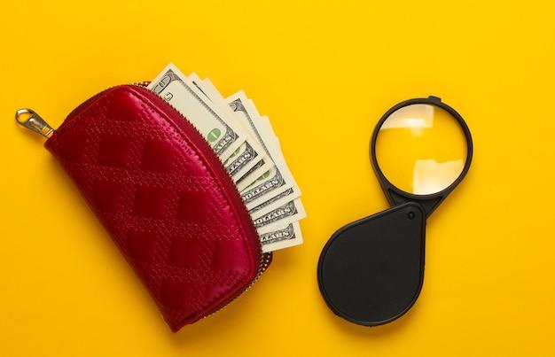 Portefeuille rouge avec billets de cent dollars et loupe sur jaune.