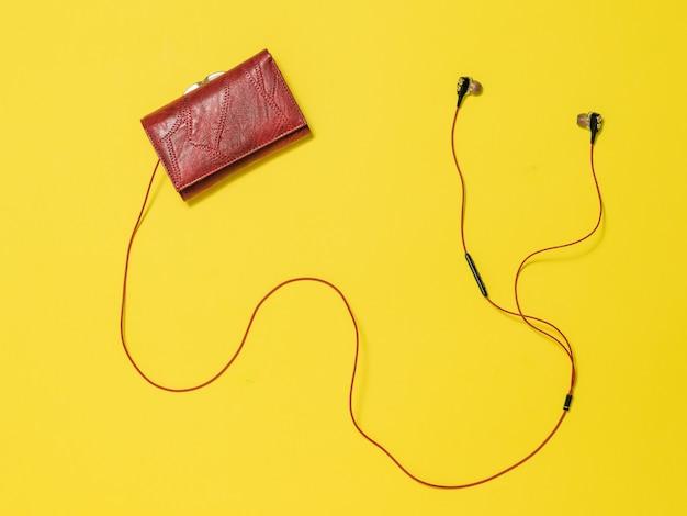 Portefeuille rouge pour femmes et écouteurs rouges sur fond jaune. accessoire féminin à la mode.