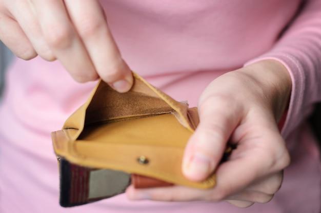 Portefeuille vide entre les mains d'une jeune femme vêtue d'un pull rose.