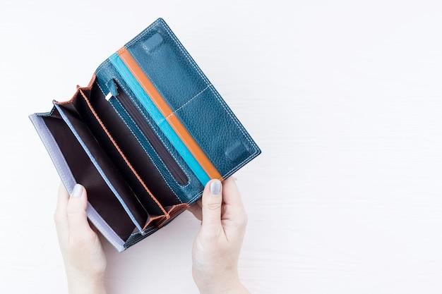 Un portefeuille vide à la main