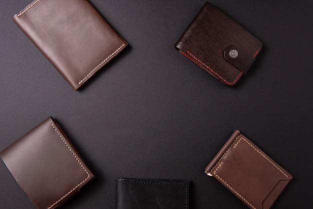 Portefeuilles en cuir sur fond noir avec un espace pour une inscription. concept d'artisanat en cuir.
