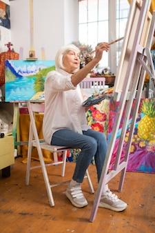 Porter des baskets élégantes. femme talentueuse âgée portant des baskets élégantes assis près de toile et de peinture