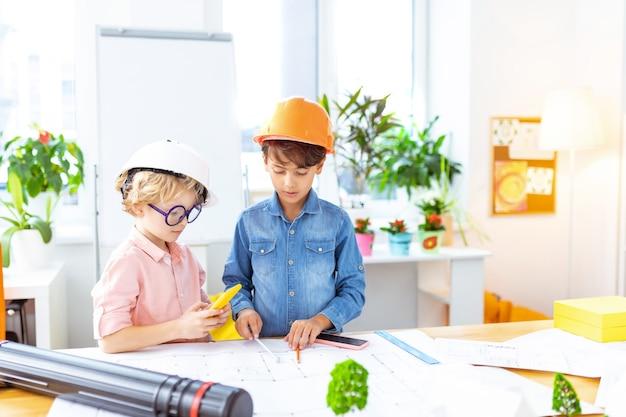 Porter des casques de protection. de mignons écoliers portant des casques de protection se sentent curieux de peindre des croquis