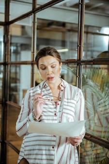 Porter des écouteurs. belle femme d'affaires enceinte aux cheveux noirs portant des écouteurs au bureau