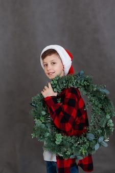 Porter d'un enfant souriant dans une chemise à carreaux rouge avec une couronne de noël. concept de nouvel an et joyeuses fêtes.
