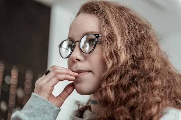 Porter des lunettes. belle adolescente aux cheveux noirs bouclés portant des lunettes et une bague noire