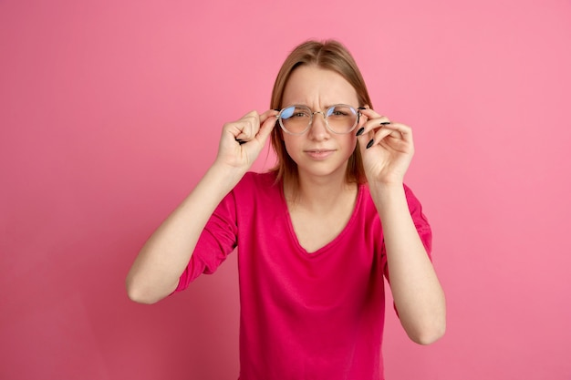 Porter des lunettes. portrait de jeune femme caucasienne isolé sur mur rose, monochrome. beau modèle féminin.