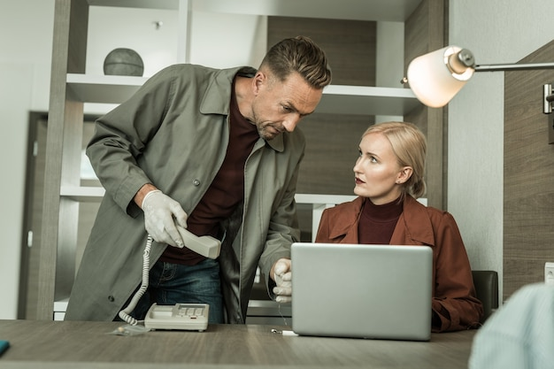 Porter un téléphone fixe. espion blonde portant toute la tenue rouge installant un programme de virus sur l'ordinateur portable à l'aide d'un lecteur flash usb