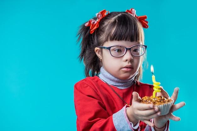 Porter des tenues colorées. attentive jeune fille avec des traits du visage et un arc rouge sur sa tête en observant le feu sur la bougie