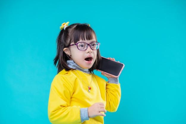 Porter des tenues colorées. surpris petite fille brune avec une anomalie chromosomique ouvrant la bouche