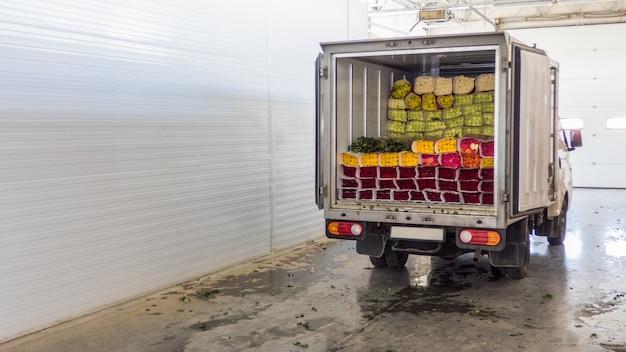 Portes arrière ouvertes du camion chargé de fleurs roses. chargement des fleurs en stock pour la livraison.