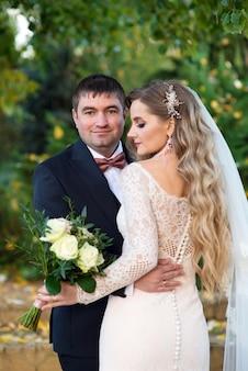 Porteur d'un beau couple de jeunes mariés dans le jardin