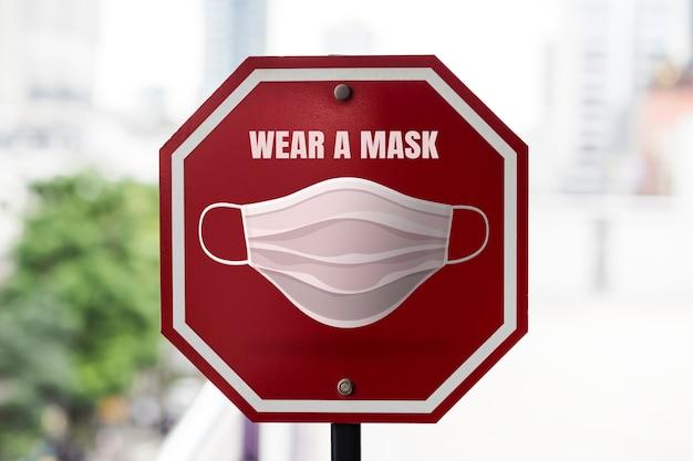 Portez un panneau de signalisation de rue de masque