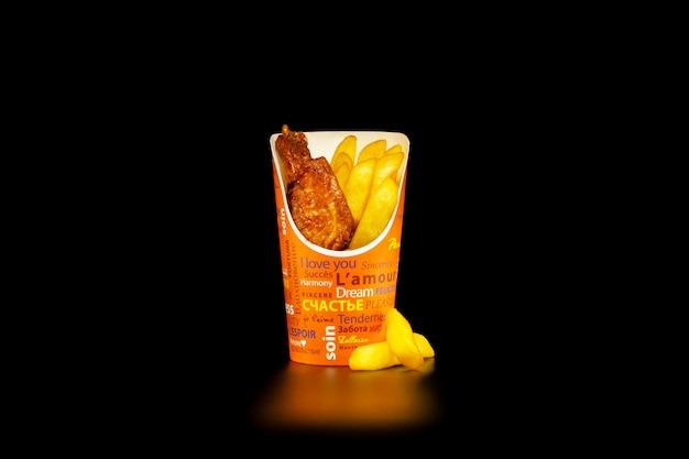 Une portion d'ailes de poulet barbecue avec des frites dans une tasse en carton