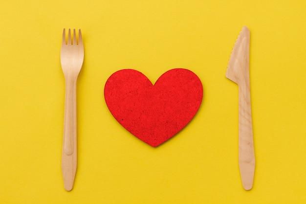 Une portion de coeur rouge avec une fourchette en bois et un couteau en bois. restaurant love concept.