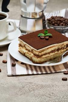 Portion de dessert tiramisu italien traditionnel et biscuits savoiardi sur table en béton gris