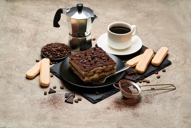 Portion de dessert tiramisu italien traditionnel et cafetière moka sur table en béton gris
