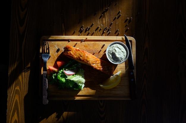 Portion de filet de saumon aux herbes sur une table en bois. vue de dessus