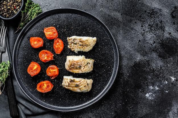 Une portion de filets de goberge ou de charbon grillés, cuits au four. fond noir. vue de dessus. copiez l'espace.