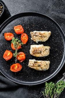 Une portion de filets de goberge ou de charbon grillés, cuits au four. fond noir. vue de dessus.