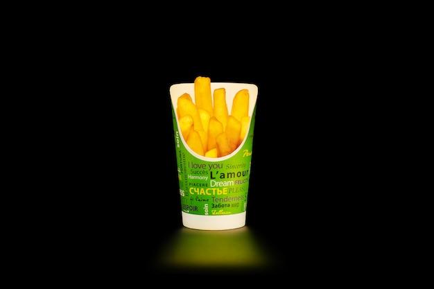 Une portion de frites dans une tasse en carton avec des inscriptions en différentes langues