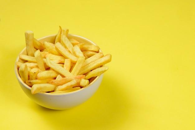 Portion de frites de pommes de terre dans un bol en céramique sur fond jaune isolé