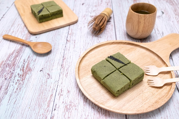 Une portion de gâteau au cannabis au thé vert matcha et de boisson au thé vert sur une assiette en bois.