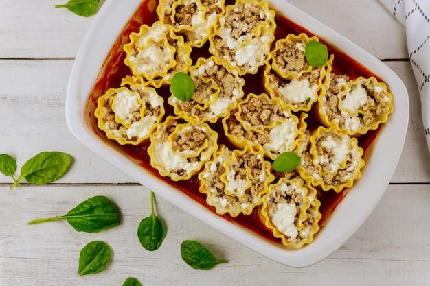 La portion de lasagne italienne se roule dans une plaque de cuisson.